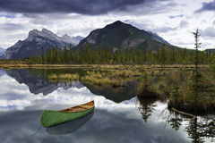 Adventure at Vermilion. A canoe is still in the reflective waters of Banff. A view across Vermilion Lakes towards Mount Rundle and the town of Banff. Banff Stock Image
