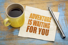 Adventure is waiting for you. Text on a napkin with a cup of espresso coffee royalty free stock image