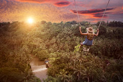 Adventure in wild jungle forest. Woman and swing. Stock Images