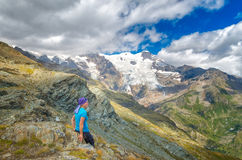 Adventure woman by glacier nature on Italy Alps. Woman hicker sits besides Alp glacier, Italy Royalty Free Stock Photo