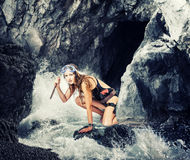 Adventure. woman with a knife in sea cave Royalty Free Stock Photography