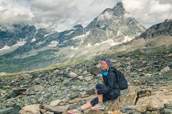 Adventure woman near Chervino with backpack  in mountain nature. Hiker girl resting on hike in mountain nature landscape in Chervinia, Alps, Italy Royalty Free Stock Image