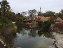 Disneyland Paris Adventureland Zone. The Adventureland zone in Disneyland Paris: a pond, a bridge, trees, the Sleeping Beauty castle is seen in the background stock photography