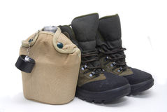 Adventurer. Canteen and boots isolated in white Royalty Free Stock Photo