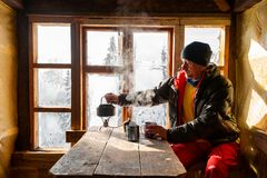 Adventurer is drinking coffee and dreaming. In a old mountain hut. Awesome winter travel in wilderness stock image