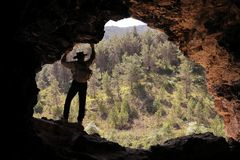 ADVENTURER EXPLORER WITH AUSTRALIAN HAT AND BACKPACK PUTTING HIS  HANDS THE ROOF OF A CAVE WATCHING A GREEN PINE FOREST stock image