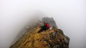 Adventurer on foggy mountain trek Stock Image