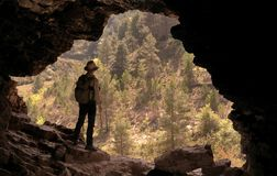 ADVENTURER WITH HAT AND BACKPACK IN A CAVE IN FRONT OF A PINE FOREST stock photo