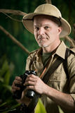Adventurer in the jungle with binoculars Stock Images