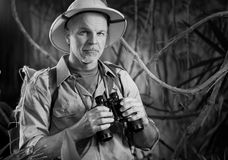 Adventurer in the jungle with binoculars Royalty Free Stock Photo