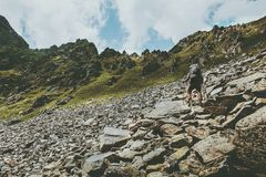 Adventurer man climbing in mountains with backpack Travel Lifestyle hiking concept summer vacations outdoor getaway. Exploring Stock Images