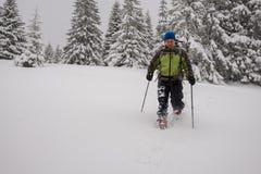 Adventurer man goes snowshoeing on deep snow Royalty Free Stock Photo