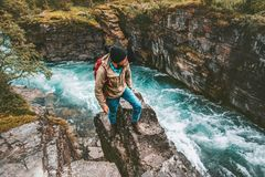 Adventurer man hiking alone active lifestyle extreme vacations. Outdoor on cliff above river canyon in Sweden royalty free stock image