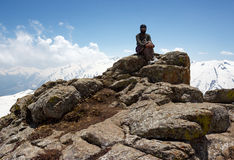 Adventurer and mountaineer. Young adventurous man and explorer poses sitting on a high rock in the snow and ice filled mountains in winter. Rocky, terrain with Stock Photo
