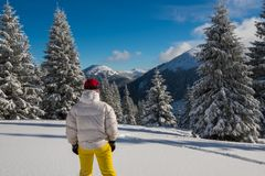 Adventurer stands among huge fir trees covered with snow. And admires amazing view of winter mountains, at wonderful sunning day - epic travel in wilderness Royalty Free Stock Photography