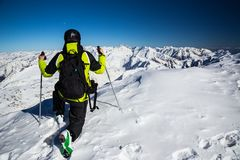 Adventurer on the top of alpine mountains. Freerider ready to running down slopes from the top of alpine mountains Stock Photo