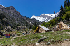 Adventurers camping, Jammu and Kashmir. A camp in the mountains, small tents by travelers who love adventure. Snow capped Himalayas behind and rocky mountains stock photos