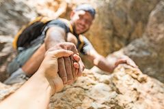 Adventurers helping each other to climb the. Help adventure other climb sport view focus royalty free stock images