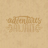 Adventures await - hand drawn lettering phrase isolated on the cardboard grunge background. Fun brush ink inscription. For photo overlays, greeting card or t Royalty Free Stock Photography