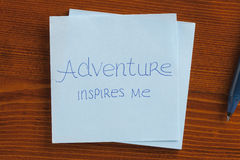 Adventures inspire me written on a note. Top view of Adventures inspire me written note on the wooden desk royalty free stock images