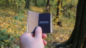Adventures or Journey Travel Trip idea. Hand holding a book with the inscription Adventure stock footage