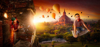 Adventures of young people stealing balloons on a magic carpet r. Adventure naughty boy stealing balloons on a magic carpet ride in Bagan (Myanmar) at sunrise Stock Image