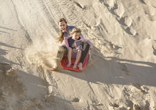 Adventuresome girls boarding down the Sand Dunes Royalty Free Stock Photo