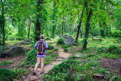 Adventuress or traveler woman go hiking on trail in forest Stock Images