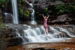 Adventurous female standing in waterfalls. Be at one with nature, breath in the waterfall, love life. Female stands in fast flowing waterfall after much rain stock photography