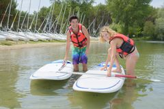 Adventurous girl taking stand up paddle class Royalty Free Stock Photos