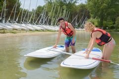 Adventurous girl taking stand up paddle class Royalty Free Stock Photography