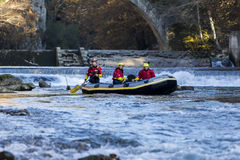 adventurous group doing white water rafting the rapids of river Stock Photography