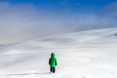 An adventurous little boy walking near the clouds on the high mountains. Child in action,on snow,in winter,near the clouds. An adventurous boy walking across the Royalty Free Stock Images