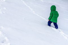 An adventurous little child walking through the snow. Winter fun in childhood Stock Images