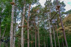 Adventurous outdoor activity at an elevated aerial forest climbing challenge course. Adventurous outdoor activity at an aerial forest climbing challenge course Stock Image