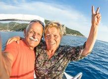 Adventurous senior couple taking selfie at Giglio Island. On luxury speedboat - Active elderly travel lifestyle concept on happy tour moment - Retired people Stock Image