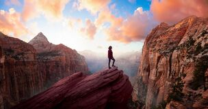 Free Adventurous Woman At The Edge Of A Cliff Is Looking At A Beautiful Landscape View In The Canyon Stock Photography - 181811032