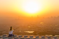 Adventurous woman sitting on top of skyscraper overlooking the city at sunrise royalty free stock photography