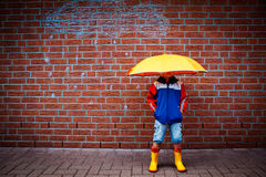 Adverse weather. A little girl with a umbrella on her head in front of a wall with a sketch of a rain cloud Stock Image