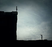 ADVERSITY. Conceptual image with two lost persons standing on a cliff at different hights, trying to find each other. Parallel world, alternate reality stock photos