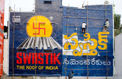 Advert painting, India. HYDERABAD, ANDHRA PRADESH, INDIA - JANUARY 6: Workmen climbing wooden scaffolding to paint colourful advertisements on January 6 2013 Stock Images
