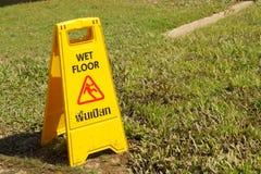 Advertencia amarilla de la muestra para el piso mojado en el parque Foto de archivo libre de regalías