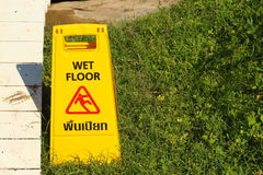 Advertencia amarilla de la muestra para el piso mojado en el parque Imagenes de archivo