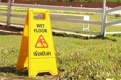 Advertencia amarilla de la muestra para el piso mojado en el parque Fotografía de archivo