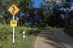 Advertencia Curvy de la señal de tráfico en el camino Imágenes de archivo libres de regalías
