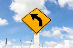 Advertencia de la curva de la izquierda en tierras de labrantío con el fondo nublado del cielo azul Foto de archivo libre de regalías