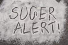 Advertencia de Sugar Alert escrita en el fondo cristalino Foto de archivo libre de regalías