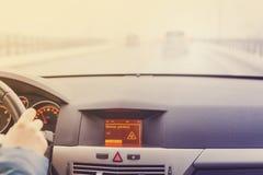 Advertencia resbaladiza del camino en la exhibición del coche Imagen de archivo