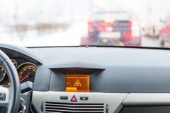 Advertencia resbaladiza del camino en la exhibición del coche Foto de archivo