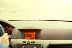 Advertencia resbaladiza del camino en la exhibición del coche Imágenes de archivo libres de regalías